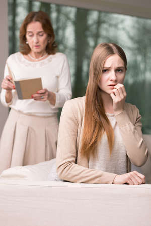 grades: Worried young girl and mother looking at her bad grades