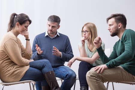 사람들은 그룹 치료하는 동안 자신의 친구를 돕고있다