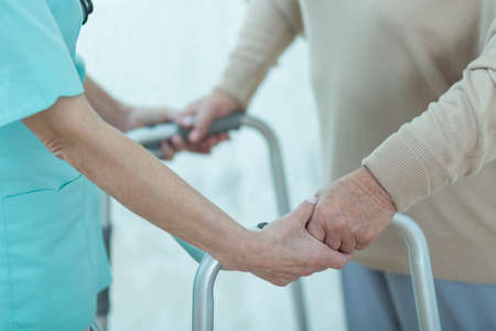 old hand: Close-up of nurse helping disabled elderly lady with a walking frame
