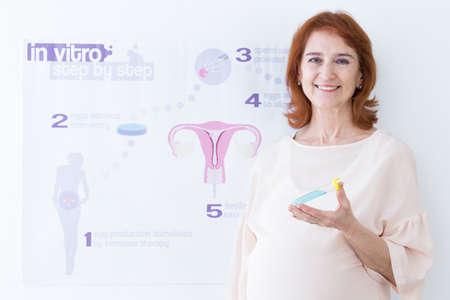 in vitro: mujer mayor feliz con el tubo de ensayo y en los pasos in vitro