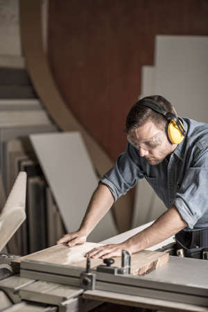 experienced operator: Vertical image of worker sawing board for furniture in carpentry