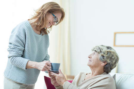 Smiling senior care assistant helping elderly lady Stok Fotoğraf