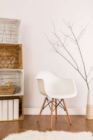 space wood: White stylish chair under twig in vase in living room