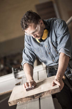 joinery: Vertical image of man working in joinery polishing up wood