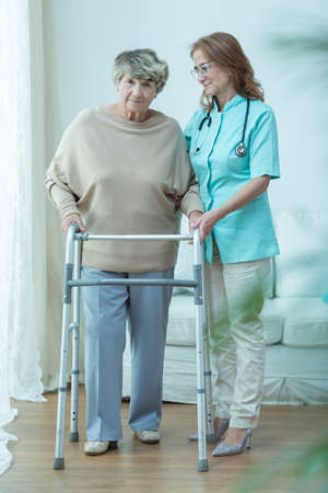 Hospital care: Care assistant and old lady with a walking frame