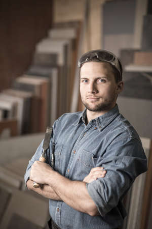 joinery: Photo of satisfied man with chisel working for joinery Stock Photo