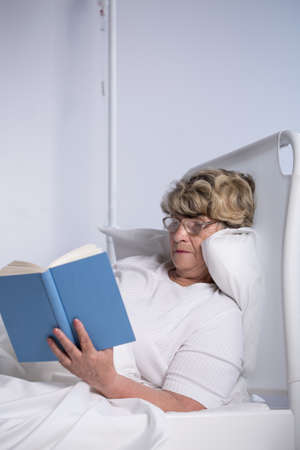 inpatient: Senior woman reading a book in hospital bed