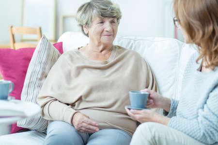 Señora mayor sonriente hablando con el trabajador social