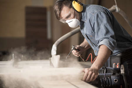 professionally: Horizontal view of professionally dressed carpenter varnishing a board