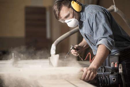 Horyzontalny widok z profesjonalnie ubrany stolarz lakierowania deski