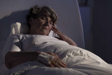 Sad elderly lady alone in hospital during night