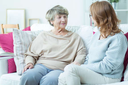 health care: Elder lady talking with caregiver in nursing home