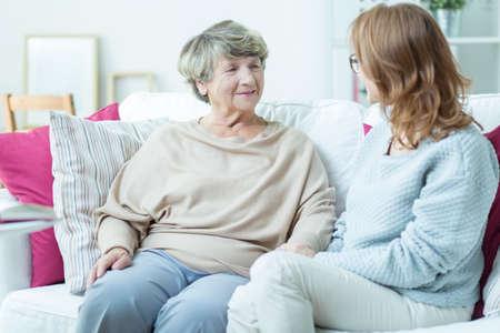Oudere dame te praten met verzorger in verpleeghuis Stockfoto