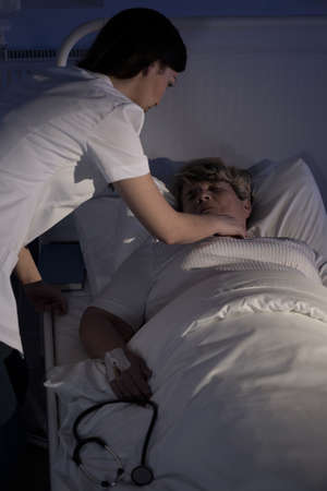 geriatrics: Young nurse helping a senior patient lying in hospital bed Stock Photo