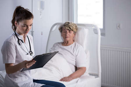 hospice: Doctor checking lab test results of elderly hospice patient
