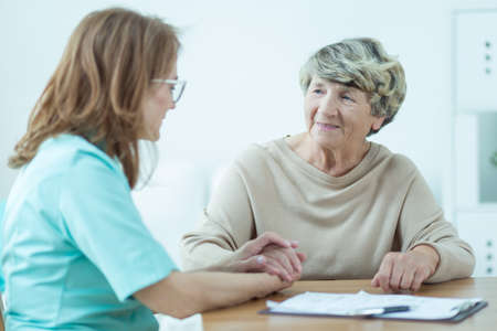 health problems: Female doctor supporting her elderly patient with health problems