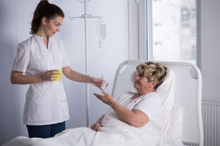 palliative: Nurse giving medicine to elderly hospice patient