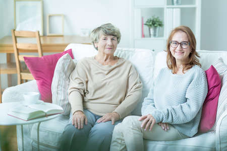 assistant: Senior care assistant sitting with elderly patient