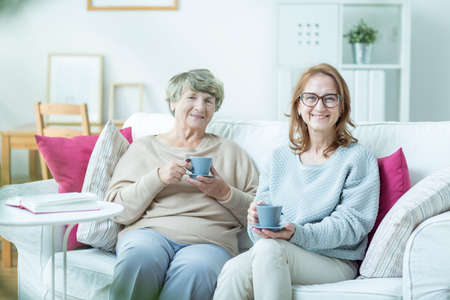 women coffee: Middle-aged woman spending time with her elderly mother Stock Photo