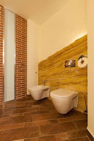 voguish: Vertical photo of loft toilet designed in natural brown tones