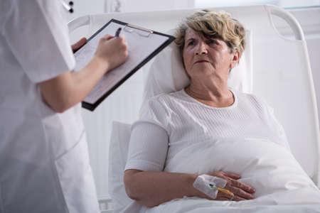 Ältere Frau im Krankenhausbett im Gespräch mit ihrem Arzt Standard-Bild
