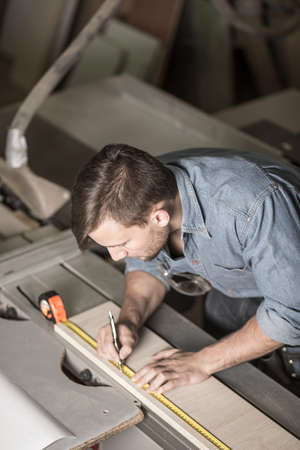 men working: Image of young brunette carpenter highlighting shape of board