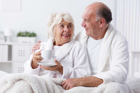 lovers embracing: Senior lovers in bed - romance in old age Stock Photo