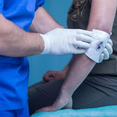 codo: Mujer con codo lesionado en la sala de tratamiento