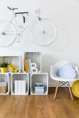 flooring: Wood, handmade furniture and bike hanging on wall in light room with flooring