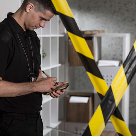 barricade: Policeman and barricade tape at the crime scene Stock Photo