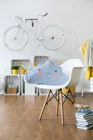 infantile: Infantile cushion lying on white chair standing in new, spacious room Stock Photo