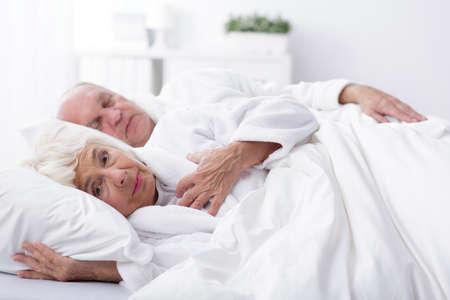 nude wife: Awaken wife and sleeping husband in bed Stock Photo