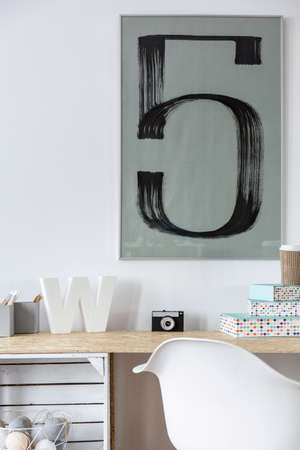 chipboard: Desk made from chipboard, white chair and poster on wall Stock Photo