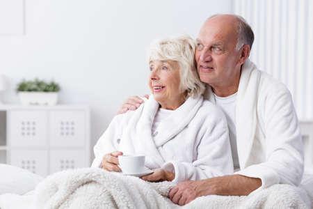 marido y mujer: Feliz pareja se retiró en la cama beber café