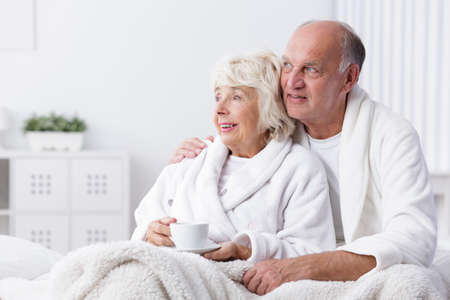 husband: Happy retired couple in bed drinking coffee