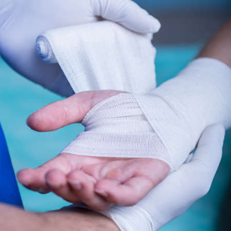 strapping: Young doctor is strapping patients arm carefully