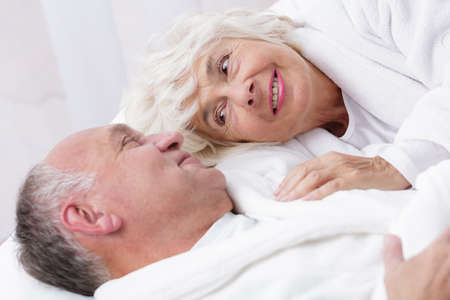romantic sex: Amorous senior couple lying together in bed