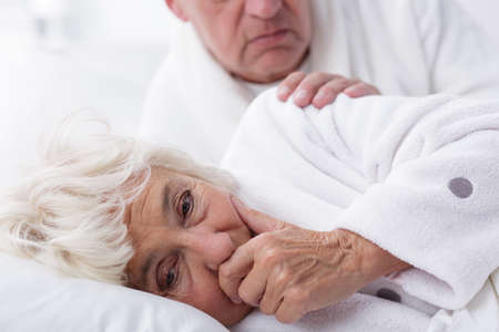 Ill woman with influenza coughing in bed