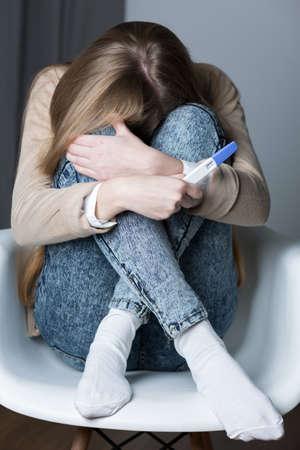 test de grossesse: Désespoir adolescent assis sur une chaise, tenant un test de grossesse positif