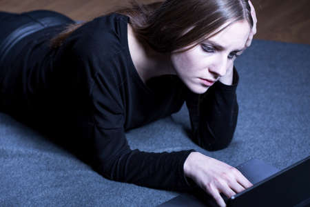 girl lying: Depressed girl in black clothes lying on floor next to laptop