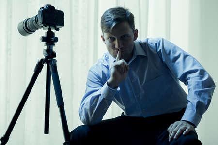 silencio: paparazzis masculino con la cámara de vídeo en el hogar Foto de archivo