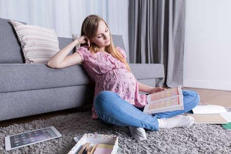 school teens: Teenage pregnant girl sitting on floor, learning for school