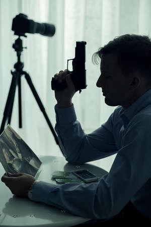 venganza: Asesino celebración de arma de fuego y mirando la imagen de víctima