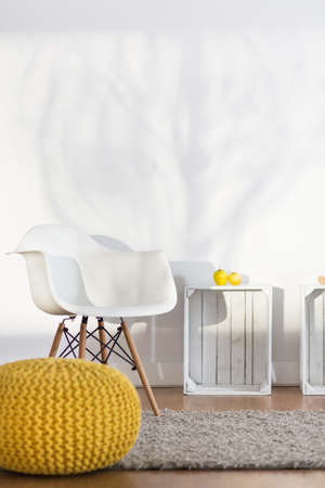 pouffe: Hand-knitted yellow pouffe, white chair, table on white background