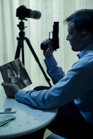 retaliation: Killer with gun watching picture of the victim Stock Photo