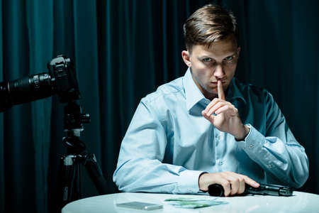 hitman: Hired killer with gun and money on table Stock Photo