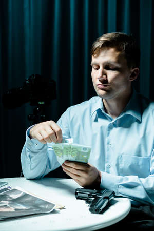 madman: Image of madman counting money for murder