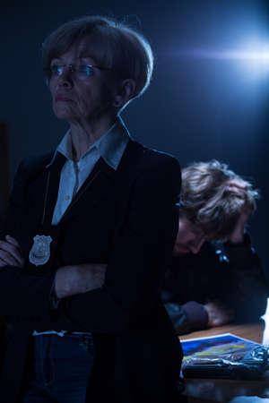 mujer policia: policía con experiencia seria con el escudo y el hombre arrestado preocupado