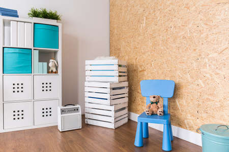 chipboard: Warm interior with wall from chipboard, regale and small blue chair