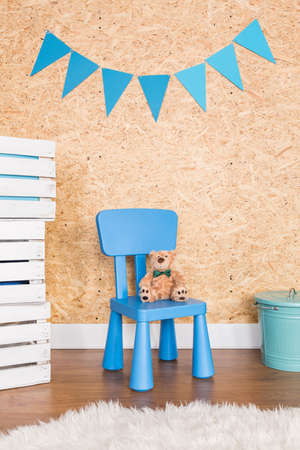 chipboard: Childish blue chair and teddy bear, chipboard wall in background